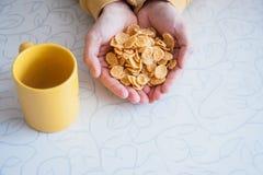 Flocos de milho e caneca amarela na tabela Imagem de Stock
