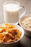 Flocos de milho e farinha de aveia nas bacias brancas com vidro do leite Imagem de Stock