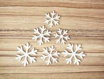 Flocos de neve brancos no fundo de madeira, decoração do inverno Fotografia de Stock Royalty Free