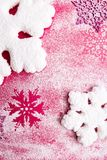 Flocos de neve cor-de-rosa e brancos em um fundo cor-de-rosa Fundo do Natal Vista superior Copie o espaço Neve decorativa Fotos de Stock Royalty Free