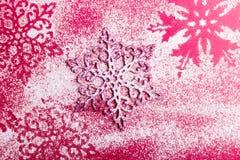 Flocos de neve cor-de-rosa e brancos em um fundo cor-de-rosa Fundo do Natal Vista superior Copie o espaço Neve decorativa Foto de Stock