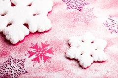 Flocos de neve cor-de-rosa e brancos em um fundo cor-de-rosa Fundo do Natal Vista superior Copie o espaço Neve decorativa Fotografia de Stock