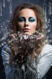 Flocos de neve de sopro da menina Fotografia de Stock