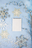 Flocos de neve decorativos de prata e um caderno em um CCB de madeira azul Fotografia de Stock Royalty Free