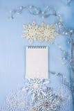 Flocos de neve decorativos de prata e um caderno em um CCB de madeira azul Imagem de Stock