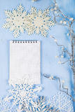 Flocos de neve decorativos de prata e um caderno em um CCB de madeira azul Foto de Stock