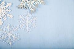 Flocos de neve decorativos de prata em um fundo de madeira azul christ Fotografia de Stock Royalty Free