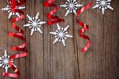 Flocos de neve e fitas vermelhas na madeira Imagem de Stock