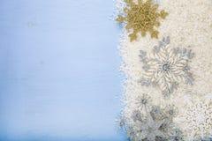Flocos de neve e neve decorativos de prata em um backgroun de madeira azul Imagem de Stock