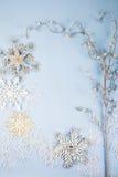 Flocos de neve e ramo decorativos de prata em um backgro de madeira azul Foto de Stock