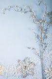 Flocos de neve e ramo decorativos de prata em um backgro de madeira azul Fotografia de Stock Royalty Free