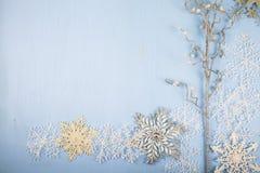 Flocos de neve e ramo decorativos de prata em um backgro de madeira azul Imagem de Stock Royalty Free