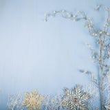 Flocos de neve e ramo decorativos de prata em um backgro de madeira azul Imagem de Stock