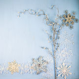 Flocos de neve e ramo decorativos de prata em um backgro de madeira azul Fotografia de Stock