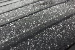 Flocos de neve em um carro preto como um fundo Imagens de Stock