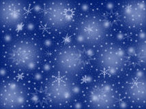 Flocos de neve em um fundo azul Imagens de Stock