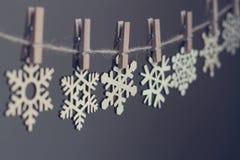 Flocos de neve de madeira em clothespegs em uma corda Fotografia de Stock