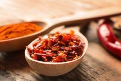 Flocos de pimenta vermelha e pó de pimentão em colheres de madeira Imagens de Stock Royalty Free
