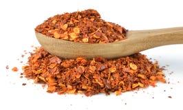 Flocos de pimenta vermelha secados, isolados no branco Imagens de Stock