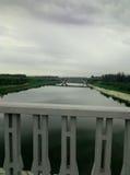 Flod för bro för gräsmattaregnhimmel Royaltyfri Bild
