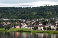 Flod, hus, skog och himmel Arkivfoto