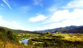 Flod i bergdalen med den ljusa ängen, naturligt sommarlandskap, blå himmel med vita moln Royaltyfria Foton