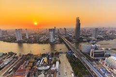 Flod i den Bangkok staden med hög kontorsbyggnad på solnedgången Royaltyfri Bild