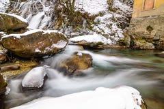 Flod i fjällängarna under vinter Arkivbild