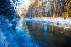 Flod i vinter Fläckigt solljus som strömmar i blandad skog arkivbild