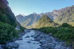 Flod längs den gröna kullen i solig dag Royaltyfri Fotografi