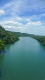 Flod med blå himmel i solig dag Arkivbild