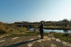 Flod med en bro i backrounden i Sabile, Lettland arkivbilder