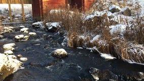 Flod med snö på stenarna framme av ett damm lager videofilmer