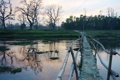 Flod- och bambubro in mot afton Fotografering för Bildbyråer