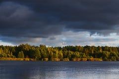 Flod och den dramatiska cloudscapen efter regnet i Lettland Arkivfoto