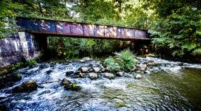 Flod och gammal bro royaltyfria foton