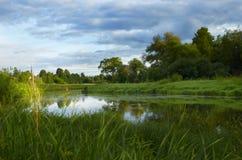 Flod och molnig himmel på sommarafton Royaltyfria Bilder