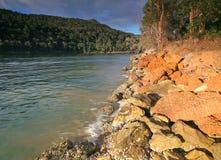 Flod som flödar förbi en sandstenbank Arkivbilder