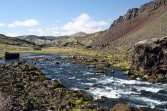 Flod som flödar till och med torrt kargt landskap, Island royaltyfria bilder
