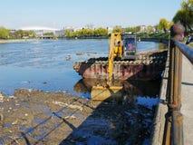 Flod som muddrar med den spårade grävskopan Royaltyfri Foto