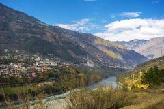 Flod som passerar till och med bergen med närliggande stadsområden royaltyfri foto