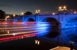 Flod tänd bro på natten med långa exponeringsljusslag arkivbild