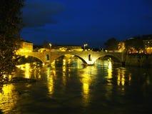 Flod Tiber på natten Bridige och byggnader Arkivfoton