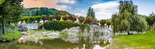 flod till och med bergby i Tuscany Arkivbilder