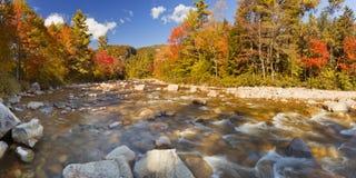 Flod till och med nedgånglövverk, snabb flod, New Hampshire, USA Arkivfoto