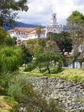 Flod Tomebamba på den torra säsongen och sikten på Todos Santos Church royaltyfri fotografi