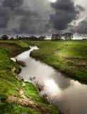Flod under en mycket tung himmel Fotografering för Bildbyråer