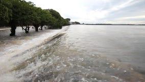 Flod vattenflöde över vägen arkivfilmer