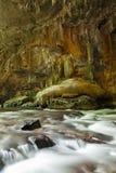 Flod vid ingången av en grotta Arkivbild