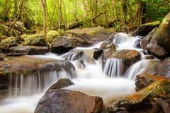 Flodbakgrund med små vattenfall i tropisk forestIt flödar från rainforestberget i bergen av Nong Bua Lam P Arkivfoto
